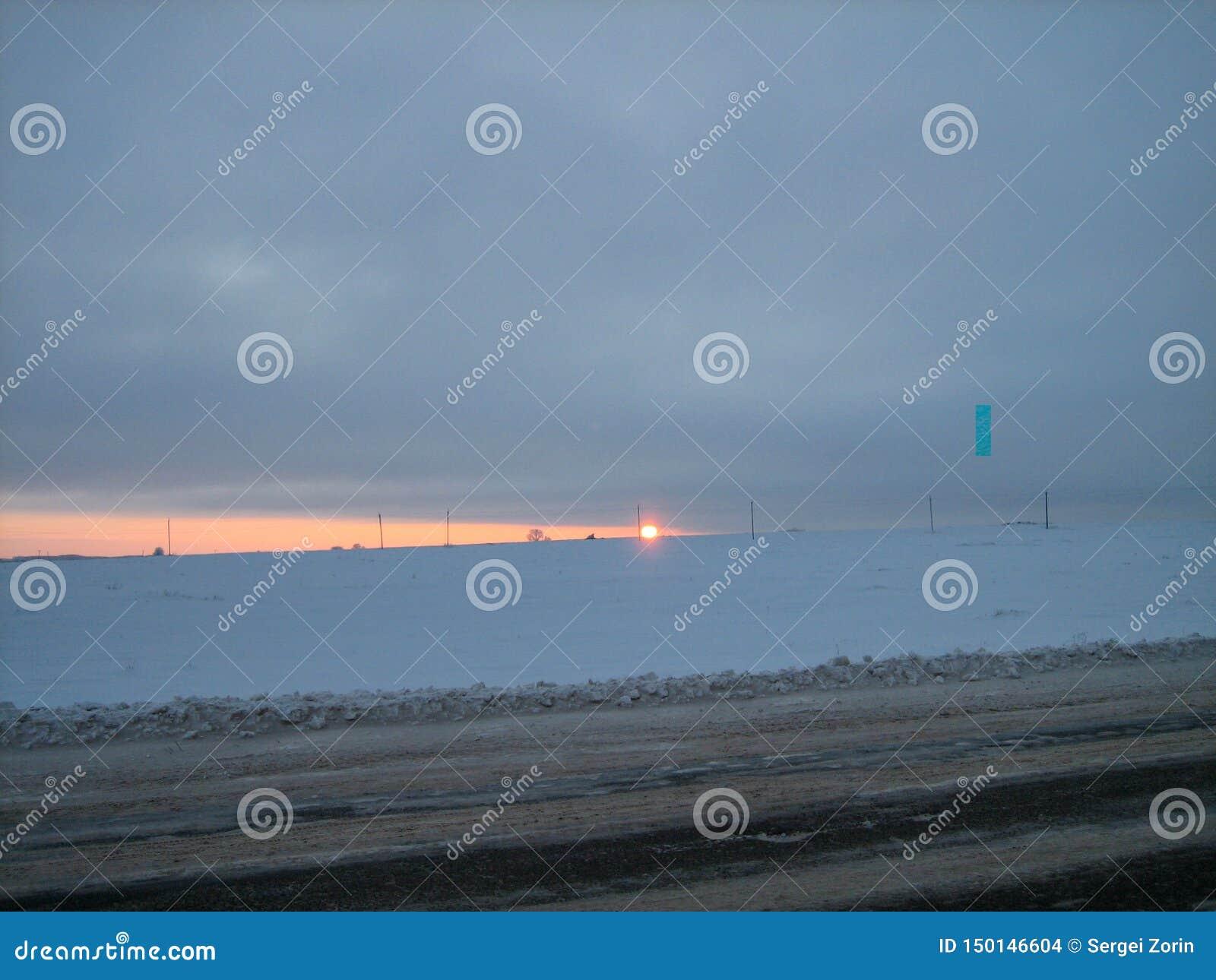 沿路的积雪的领域在日落的冬天晚上