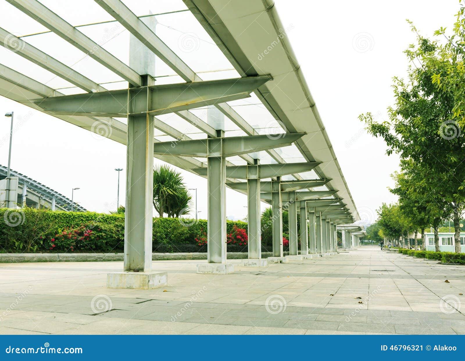 沿路面或边路的现代长的雨走廊在城市街道一边