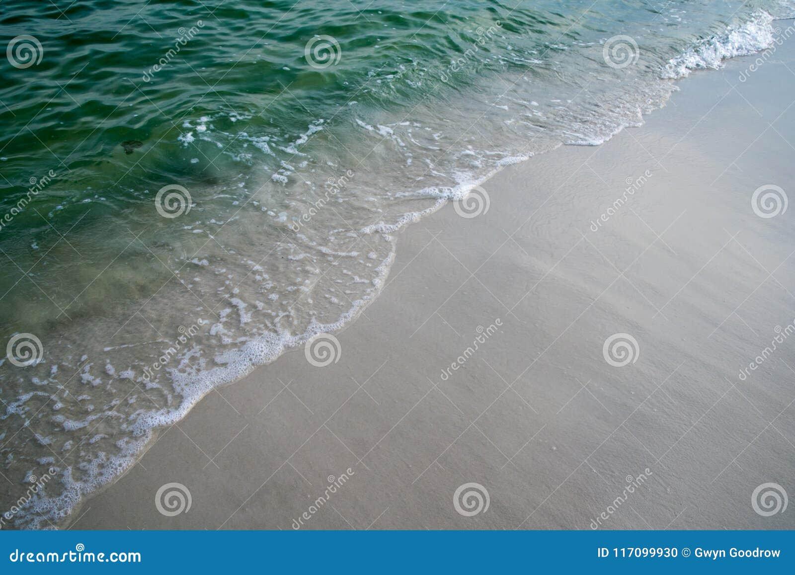 泡沫似的水推进的波浪在海滩上的