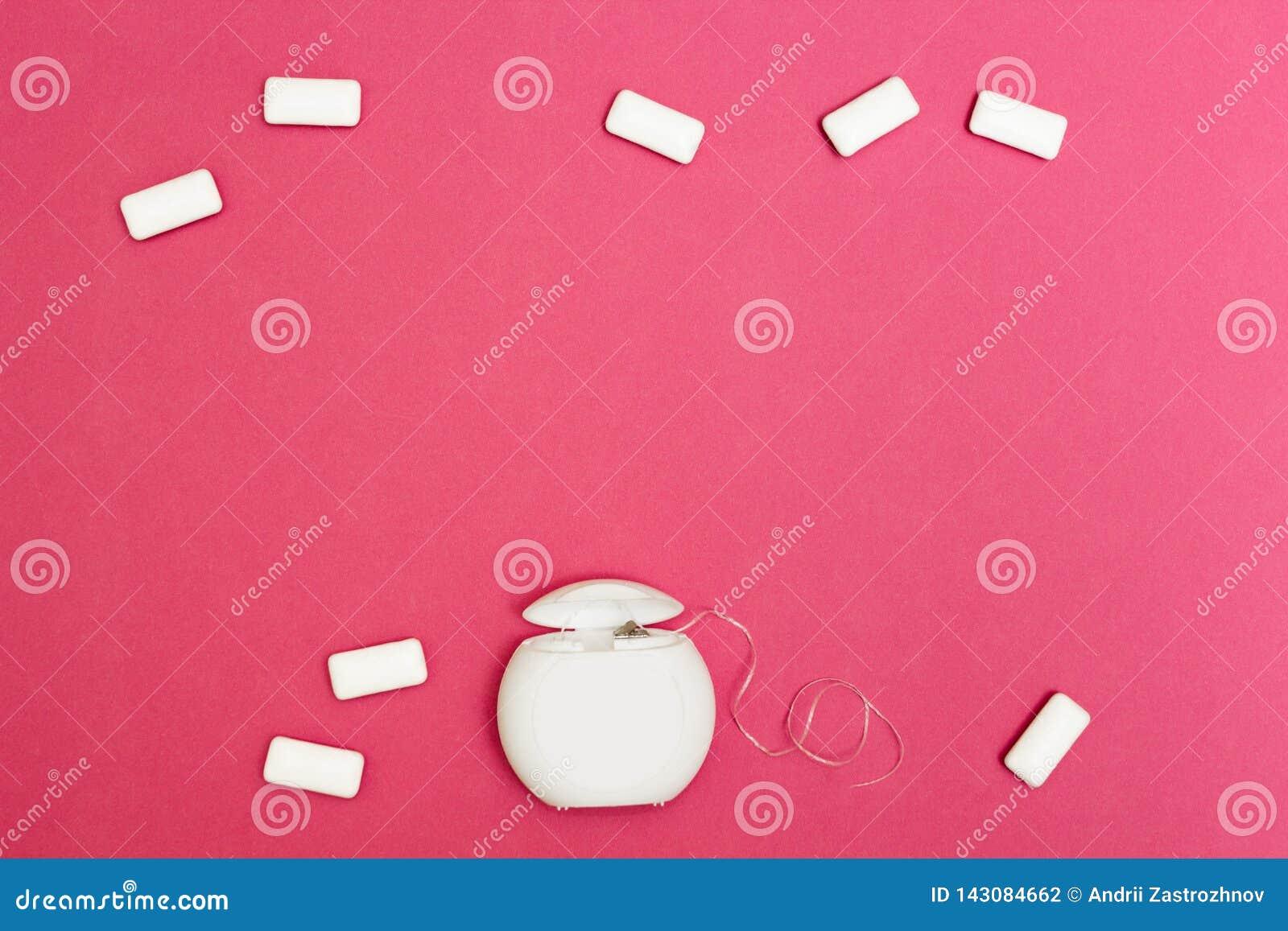 泡泡糖和牙线在桃红色背景 文本的空间