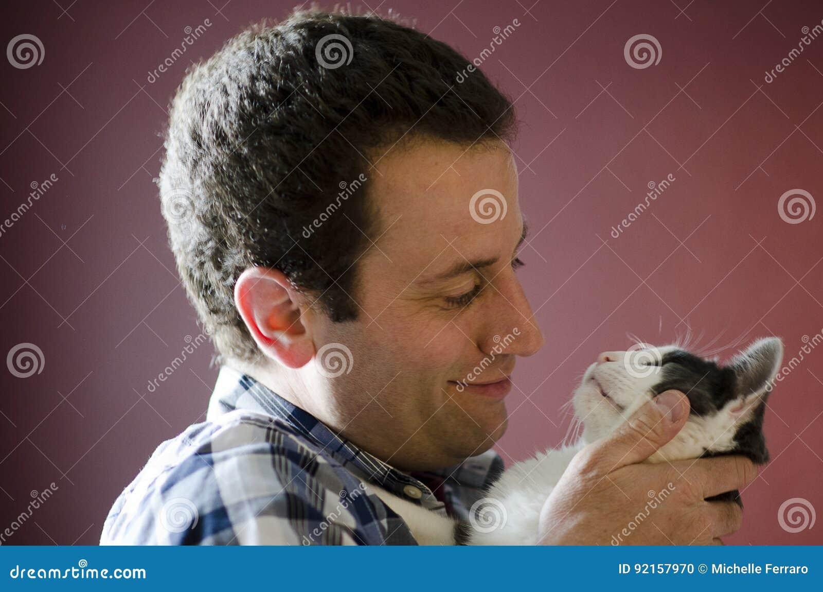 注视入彼此的人和他的猫侧视图` s注视