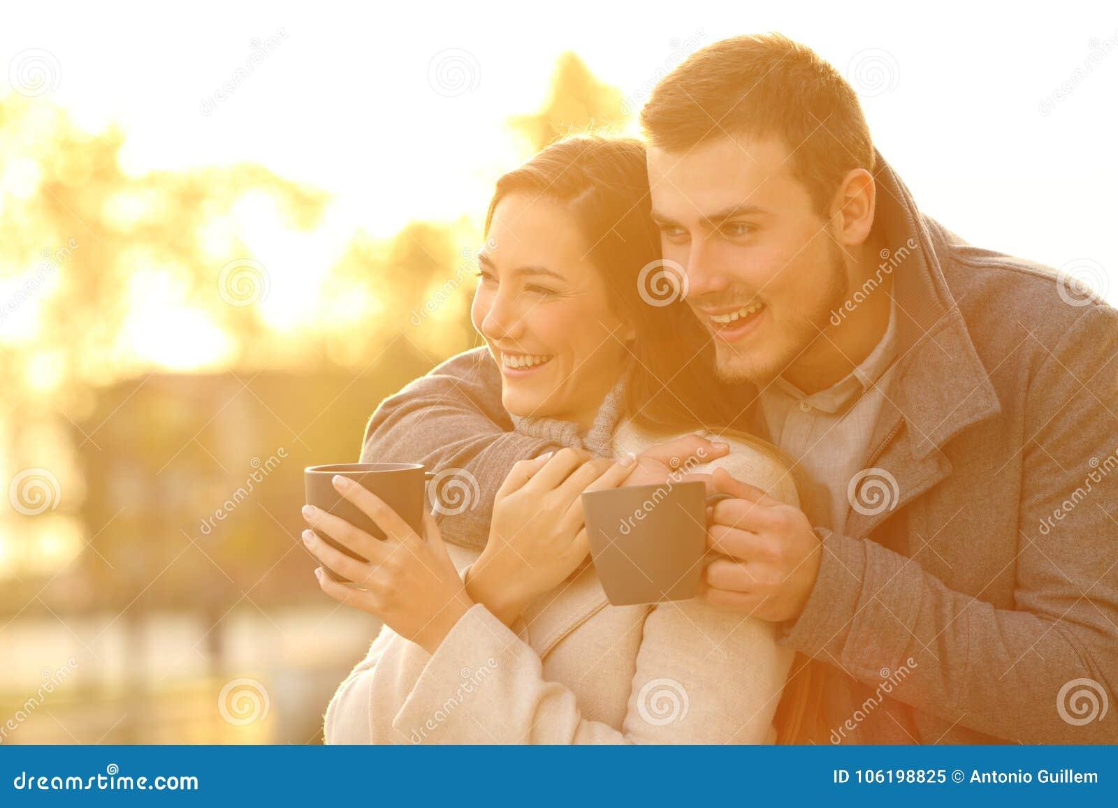 注视着在冬天的愉快的夫妇日落