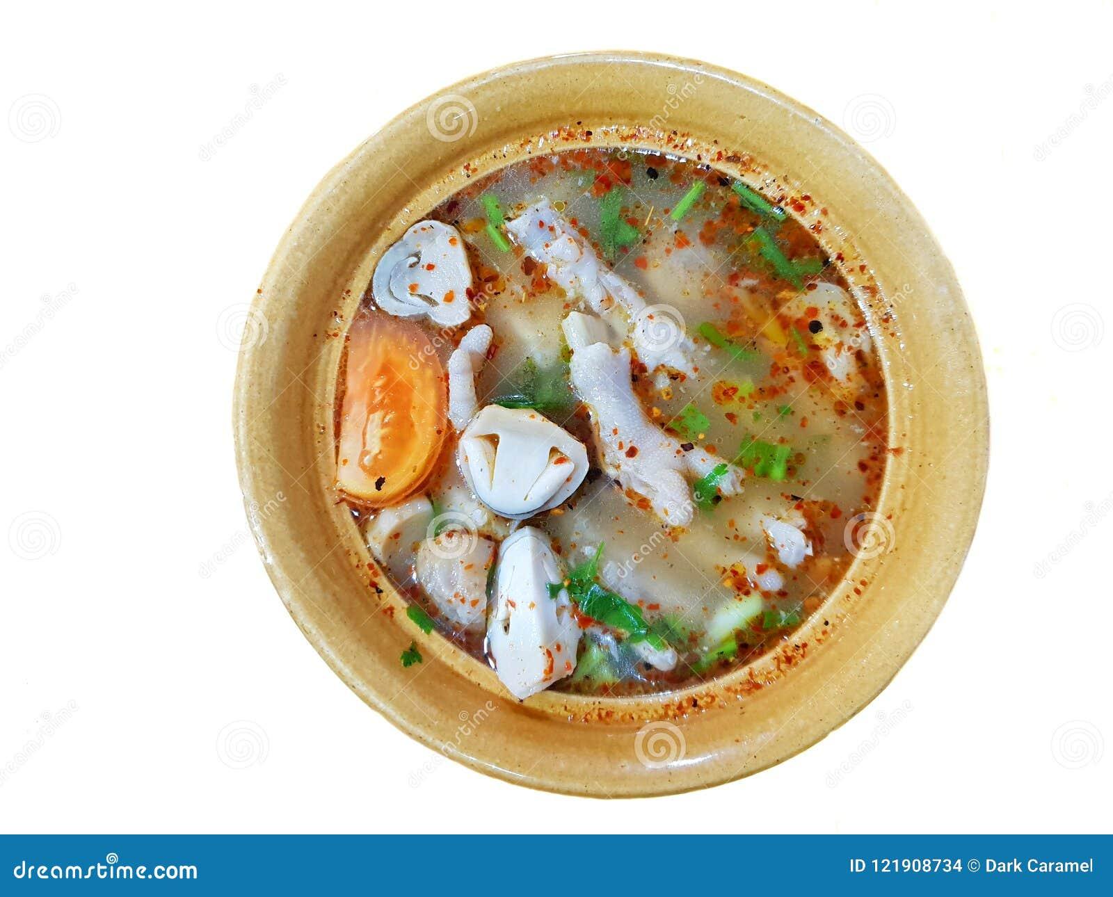 泰国食物样式、鸡脚辣汤顶视图用蕃茄,蘑菇、辣椒和香菜在被隔绝的黄色碗