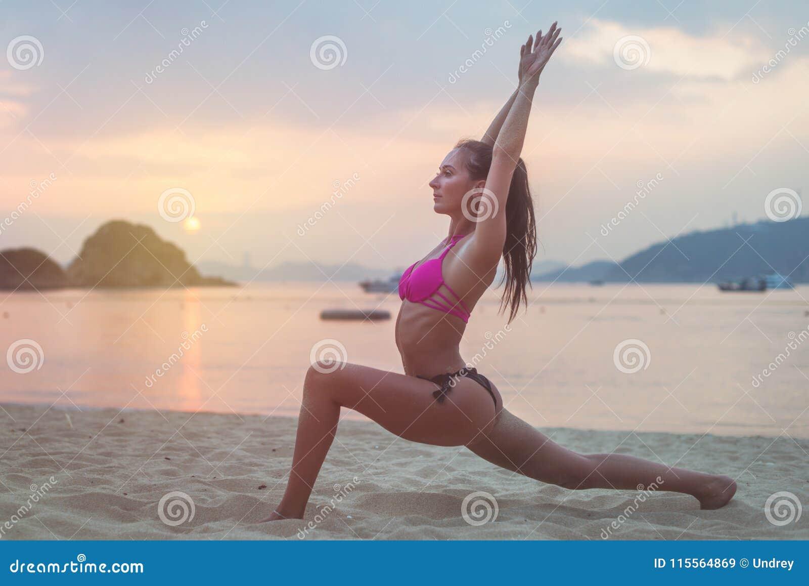 泳装的少妇行使在海滩的舒展她的腿在日落期间海上 做锻炼的健身女孩