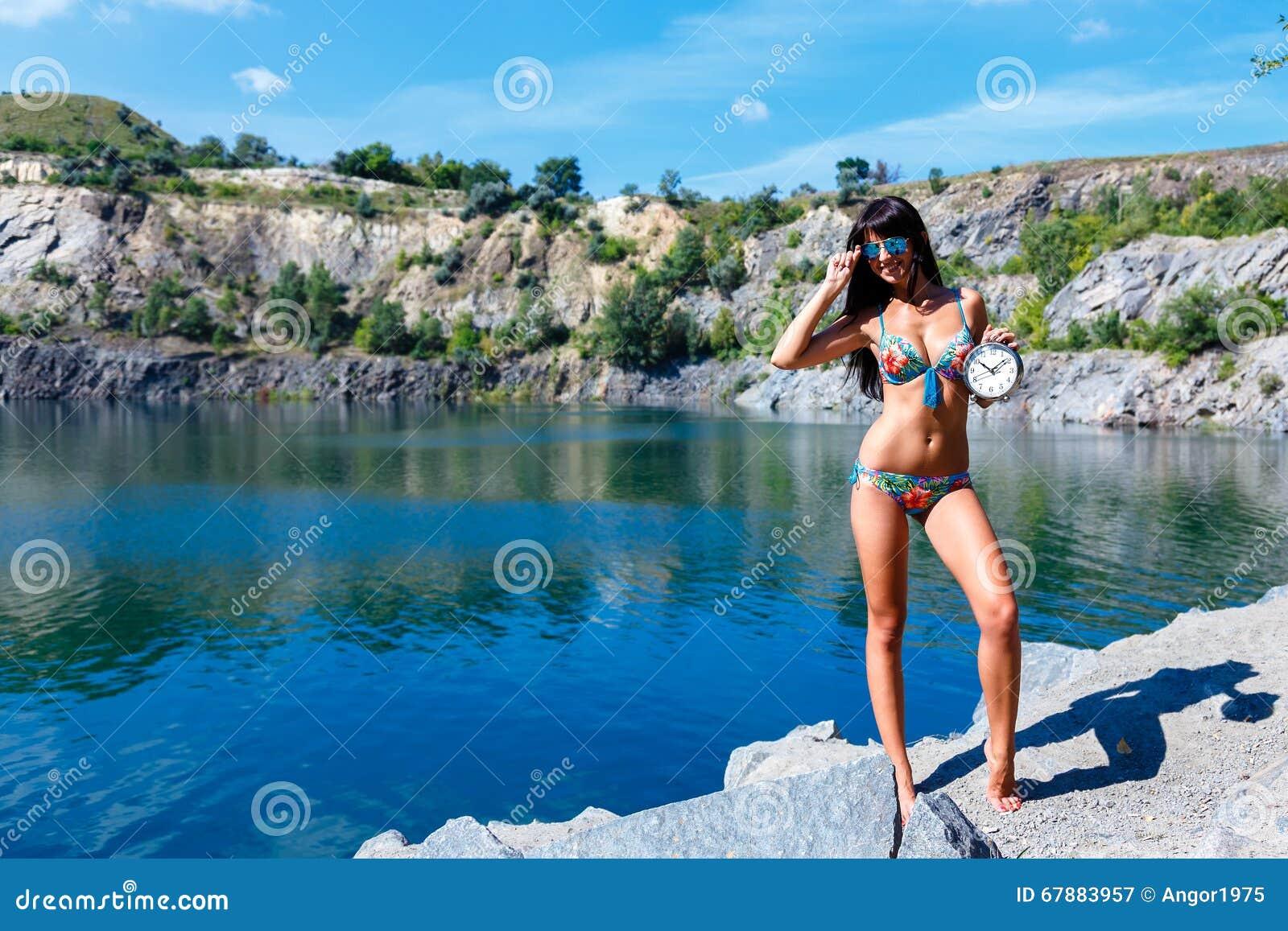 泳装的性感的微笑的女孩在拿着时钟的山河