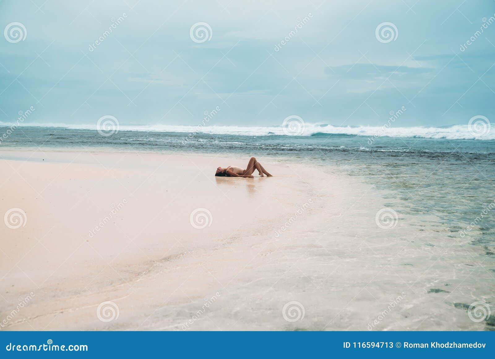 泳装的美丽的女孩在与白色沙子的海滩说谎 性感式样晒日光浴在度假在海洋附近的