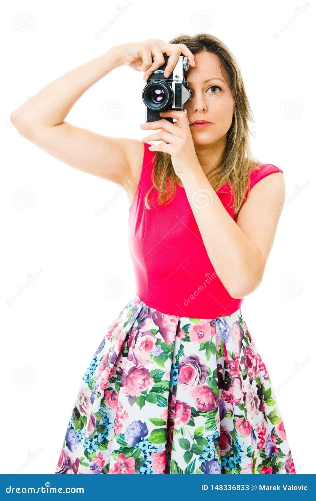 洋红色礼服的一位妇女摄影师有葡萄酒模式照相机的