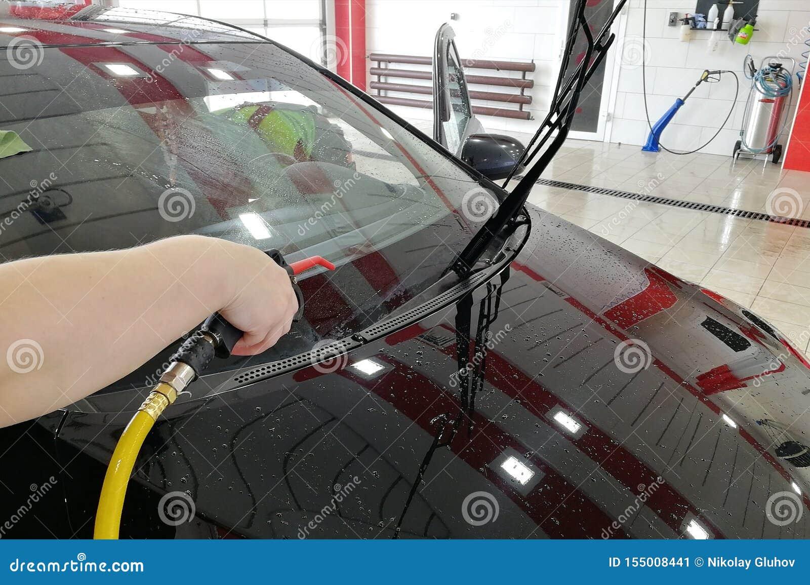 洗车工作者吹汽车的前面有压缩空气的