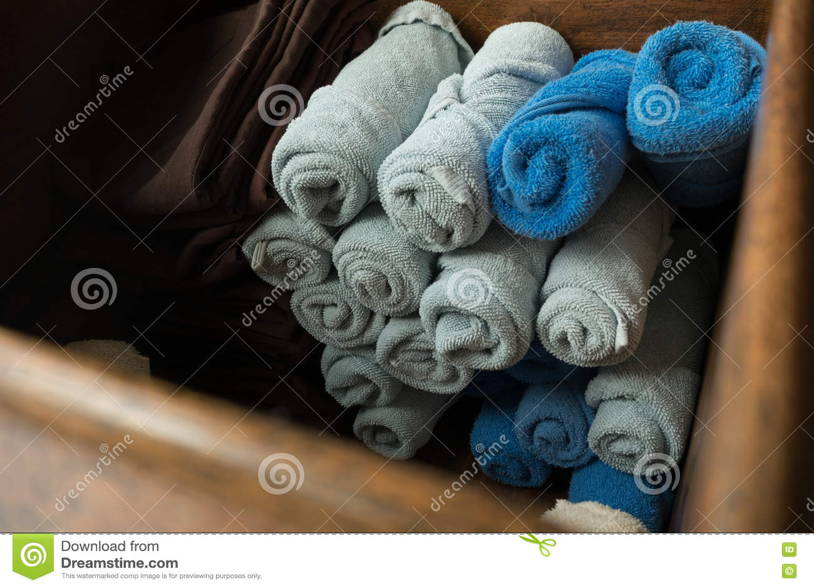 浅灰色和蓝色滚动了温泉在木箱的按摩毛巾