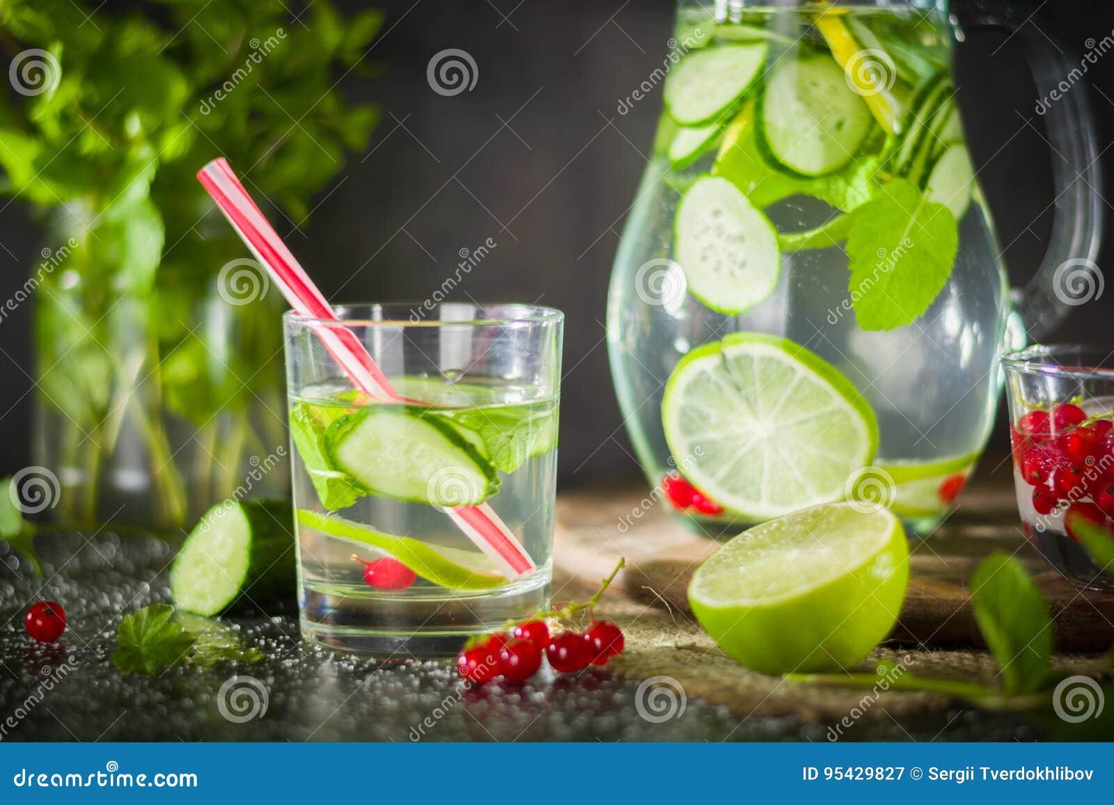 浇灌在一个玻璃瓶子和玻璃的戒毒所 新鲜的绿色薄菏和莓果 刷新和健康饮料