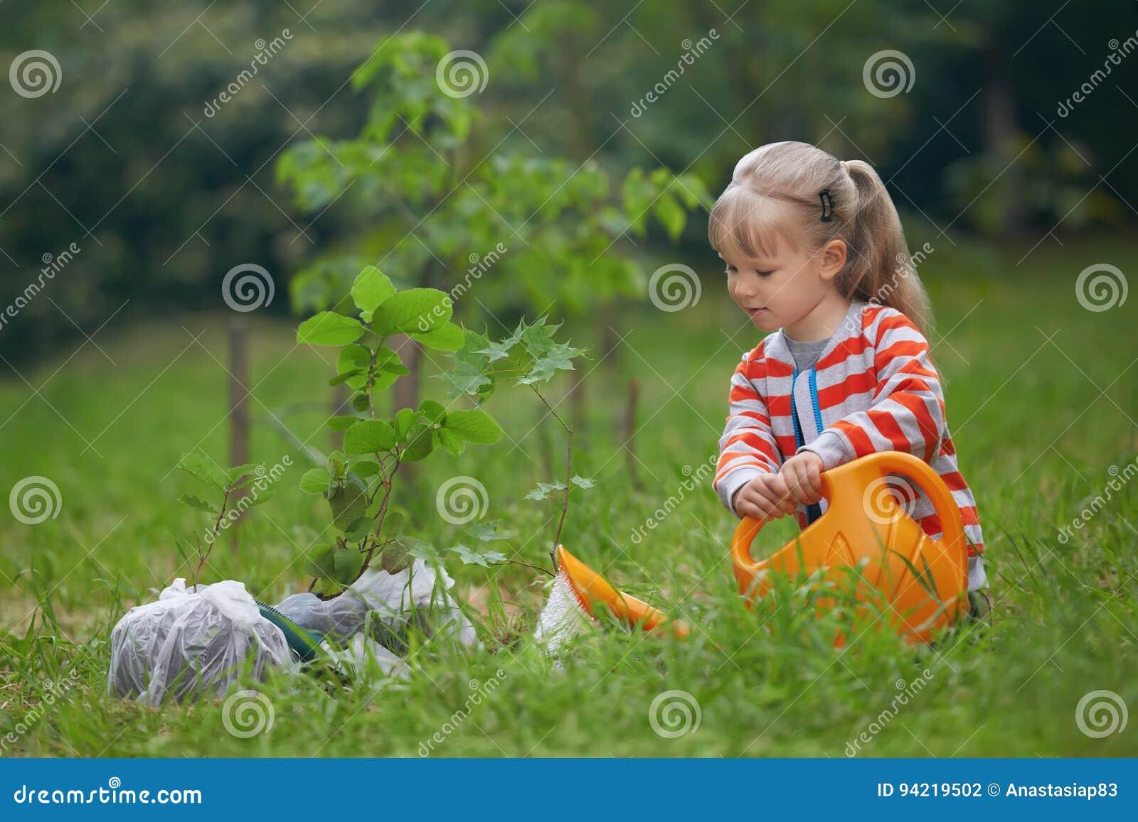 浇灌被种植的树的孩子