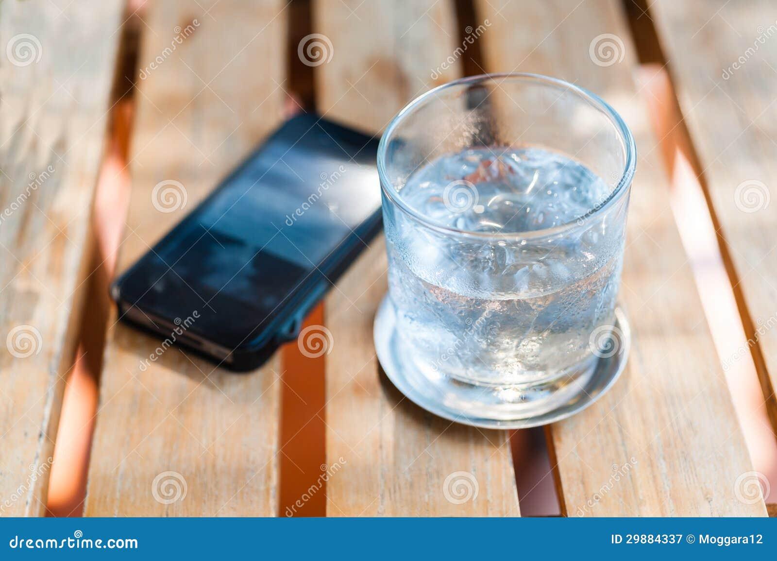 浇灌在玻璃的饮料与在木桌的电话
