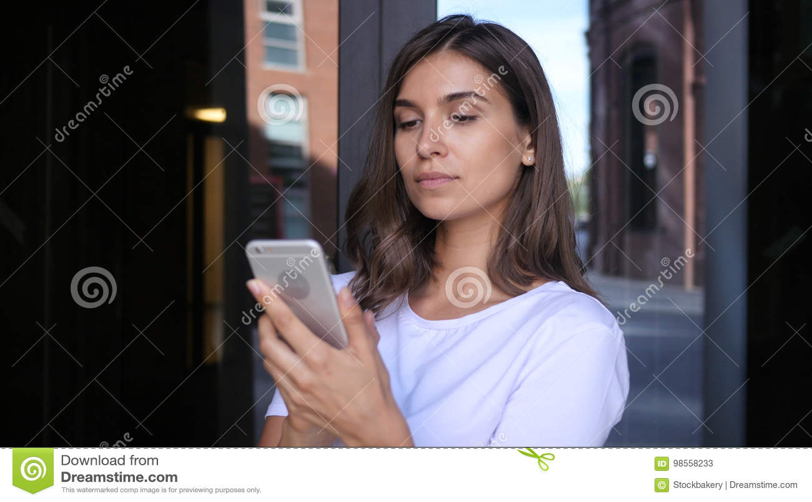 浏览在智能手机的美丽的女孩,使用电话