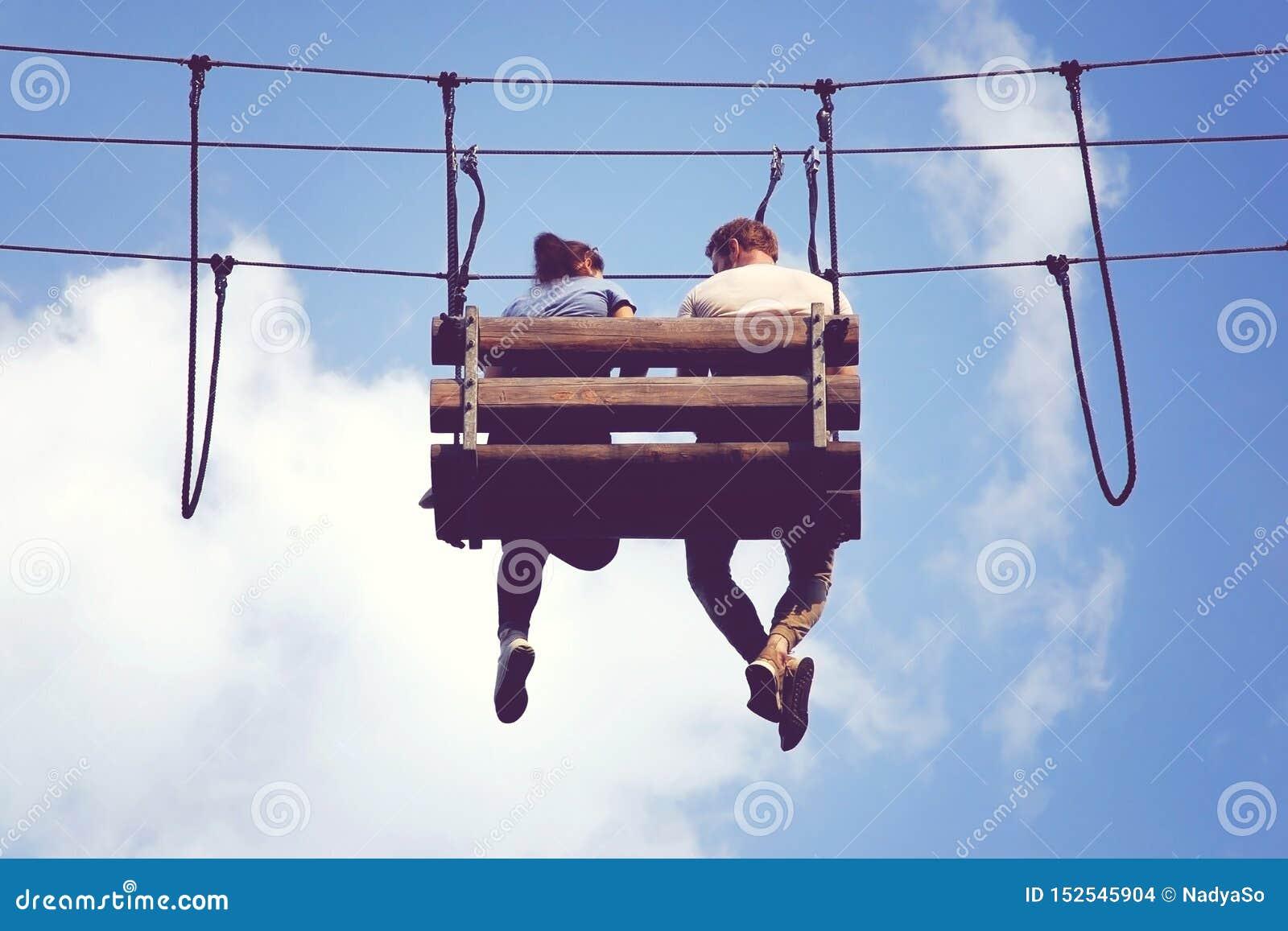 浪漫会议在天空,在一条垂悬的长凳的夫妇坐的摇晃的脚