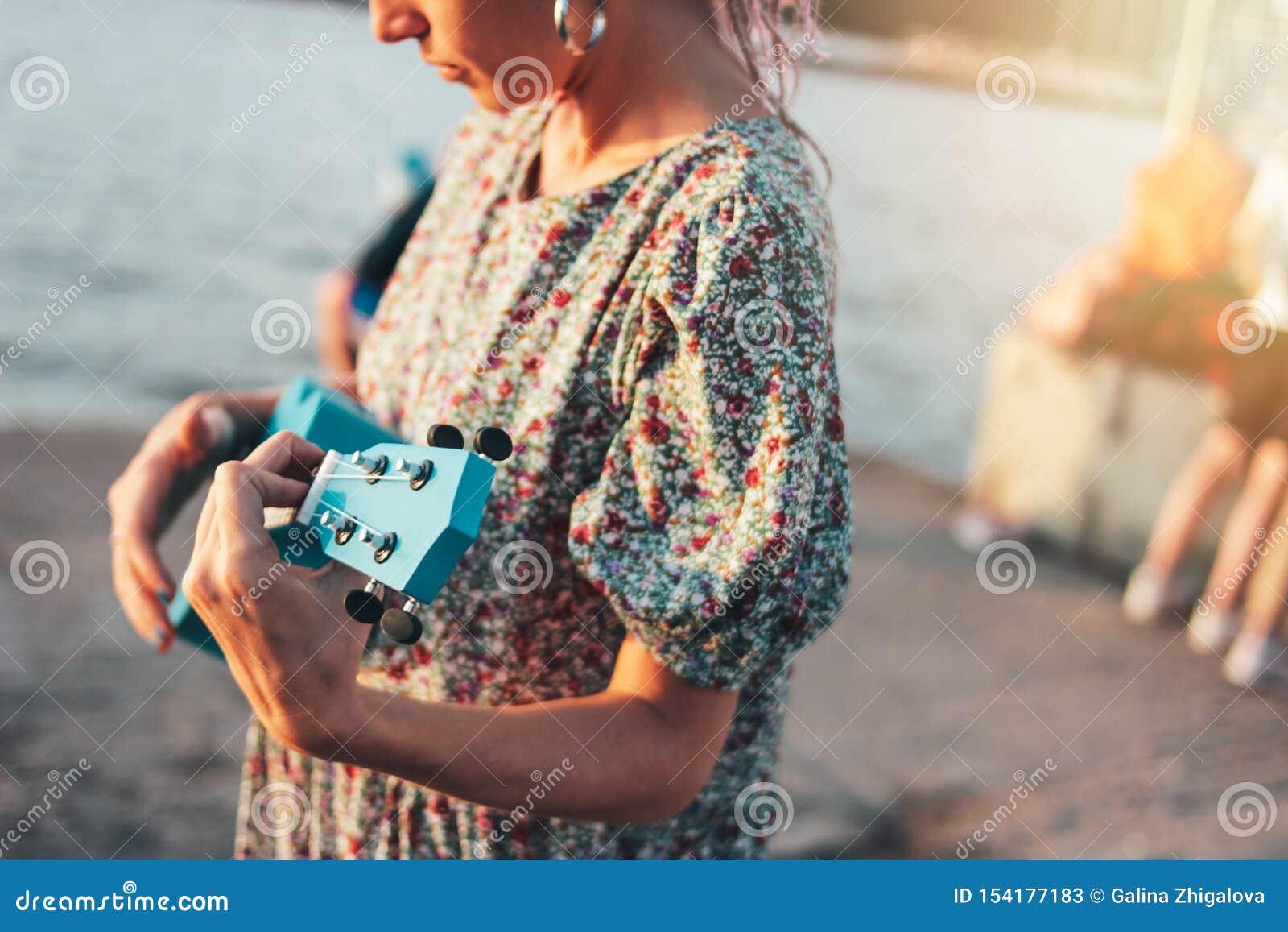浪漫年轻女人音乐家庄稼照片有非洲辫子的在使用在日落海滩的尤克里里琴的礼服