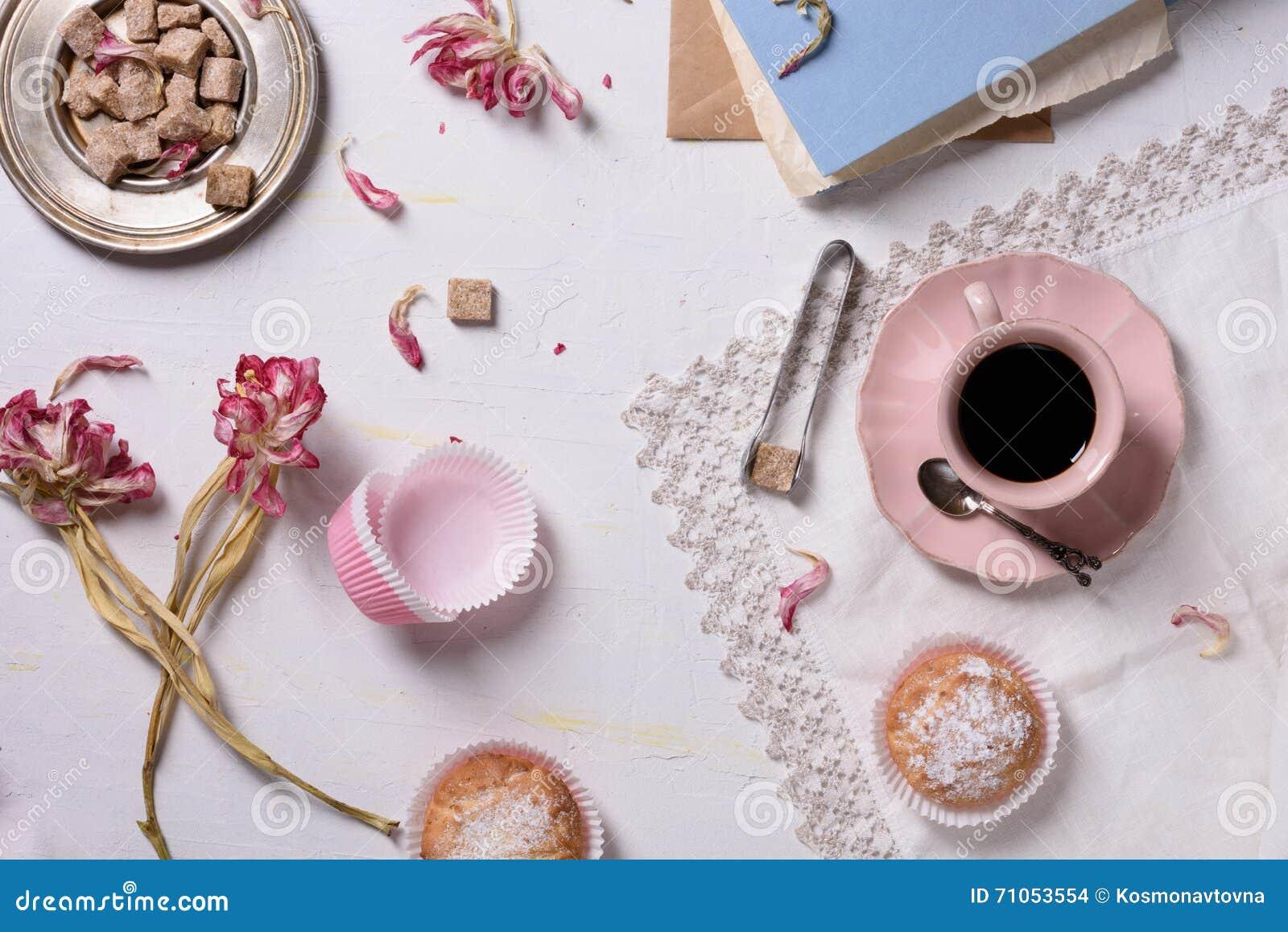 浪漫早餐、新鲜的咖啡、杯形蛋糕点心和桃红色花服务充满爱 顶视图