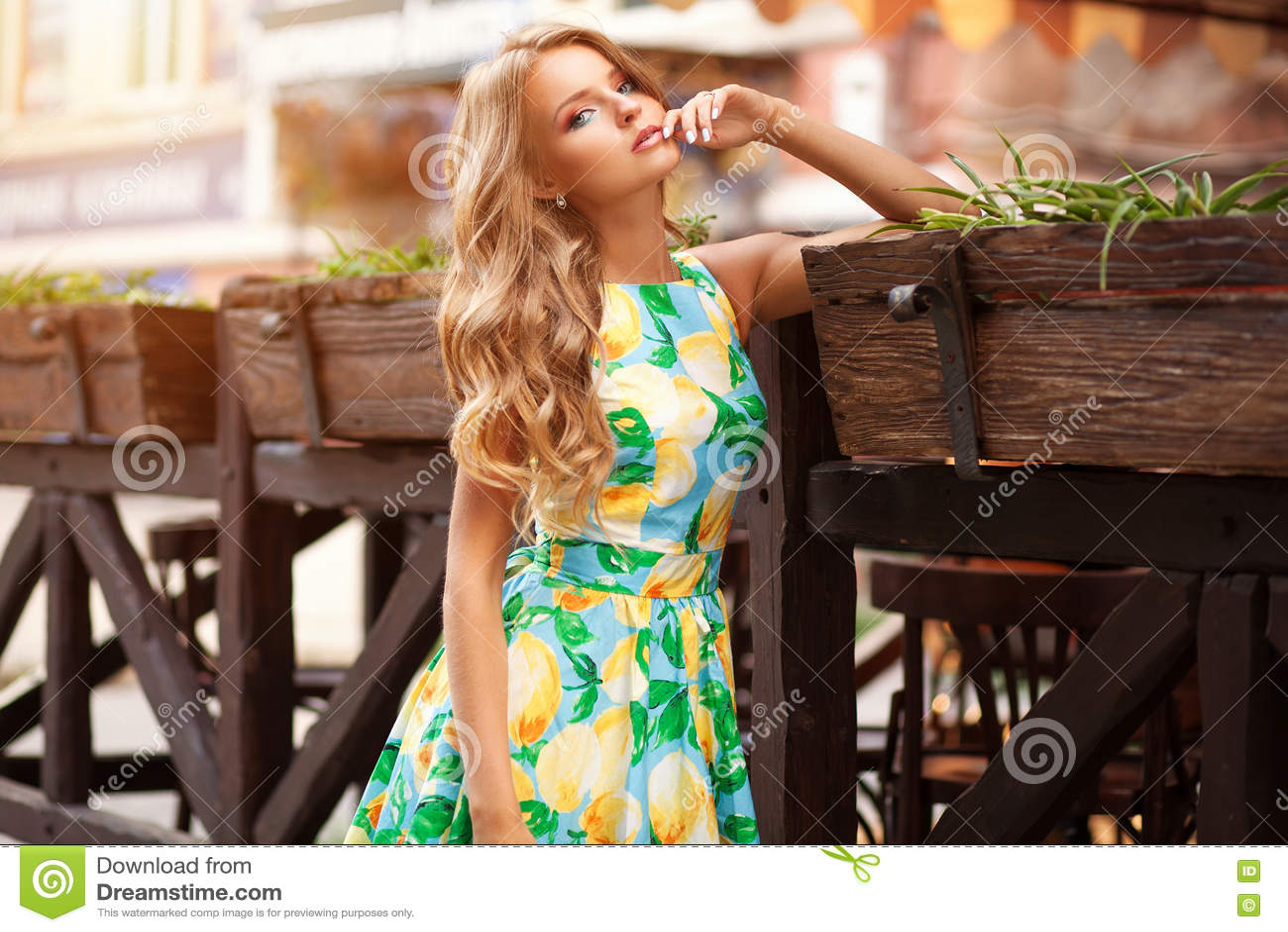 浪漫礼服的美丽的端庄的妇女在与花的咖啡馆
