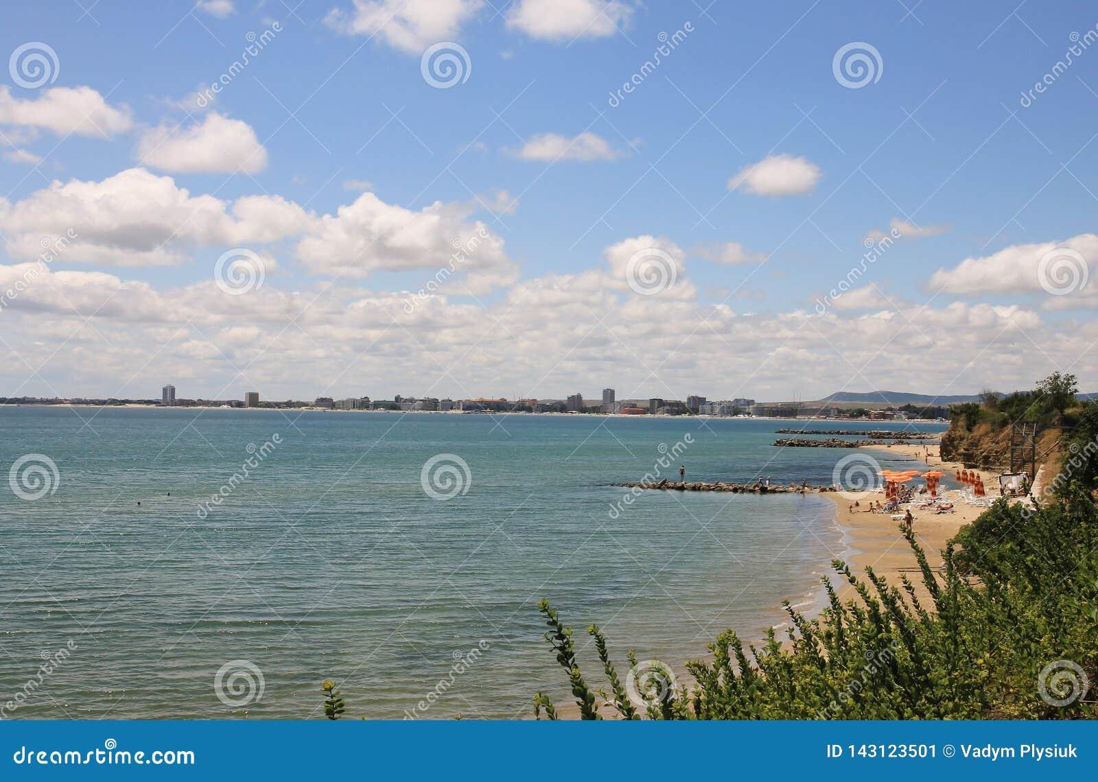 海和绿草的夏天风景 沙滩和大海与天空和白色云彩 晴朗的海滩在的保加利亚