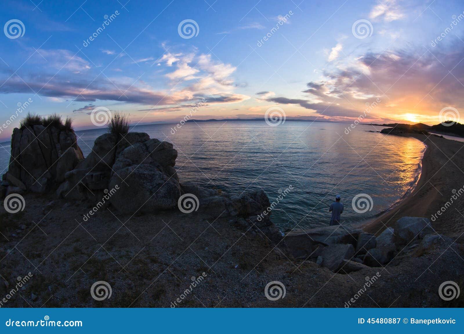 海岩石cloudscape的剪影和反射在日落的