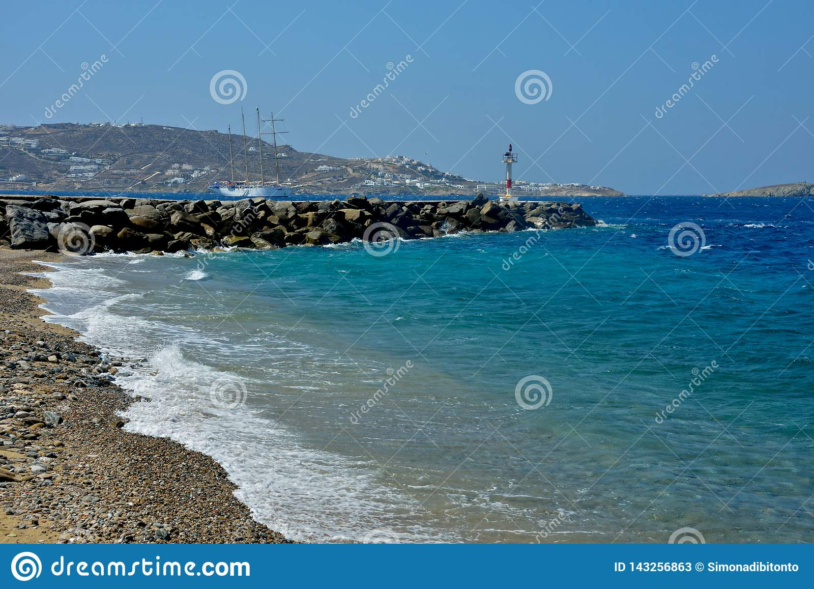 海景在从与码头的一小卵石bech看见的米科诺斯岛用轻的设备和一艘帆船