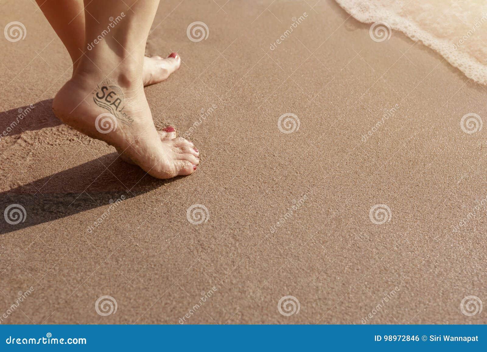 海有纹身花刺的恋人妇女走在沙子海滩的在日落期间