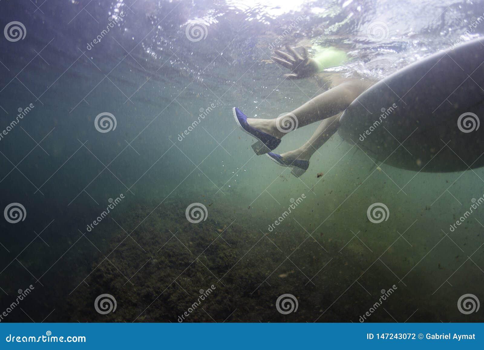 海浪女孩坐有鞋子的一个冲浪板在水面下