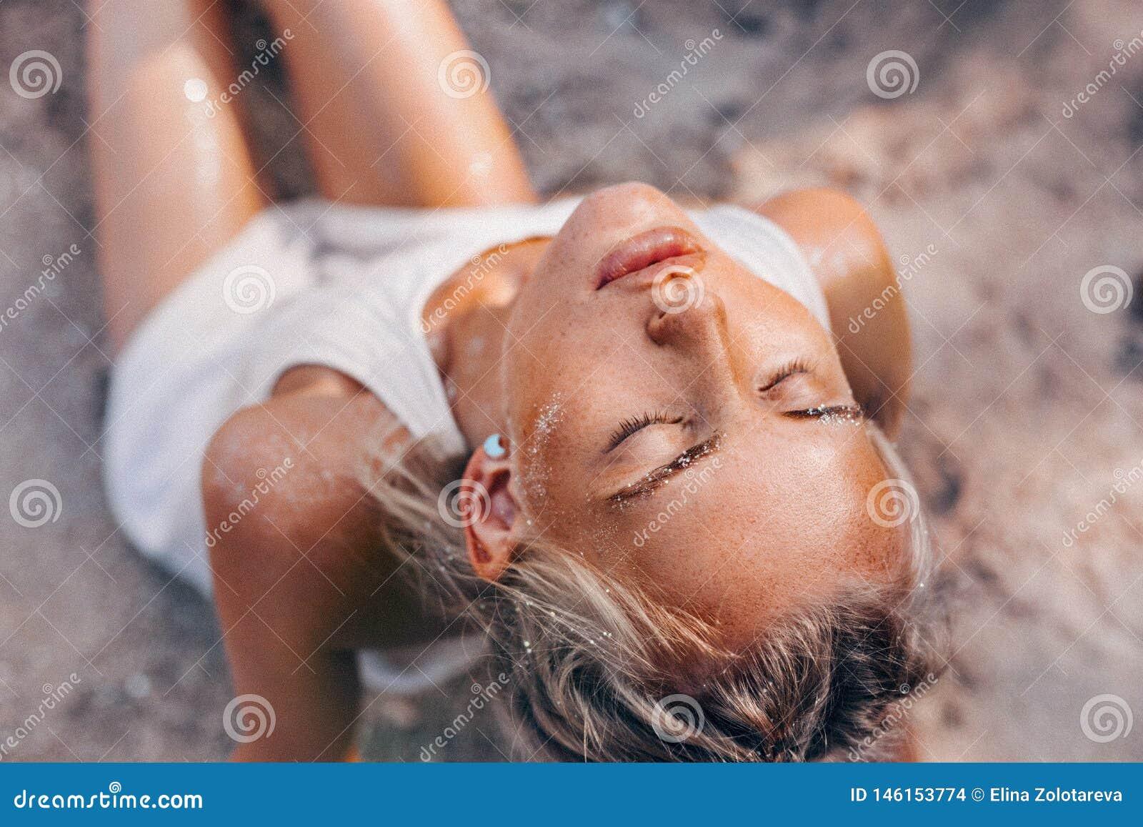 海滩关闭的美丽的年轻女人画象