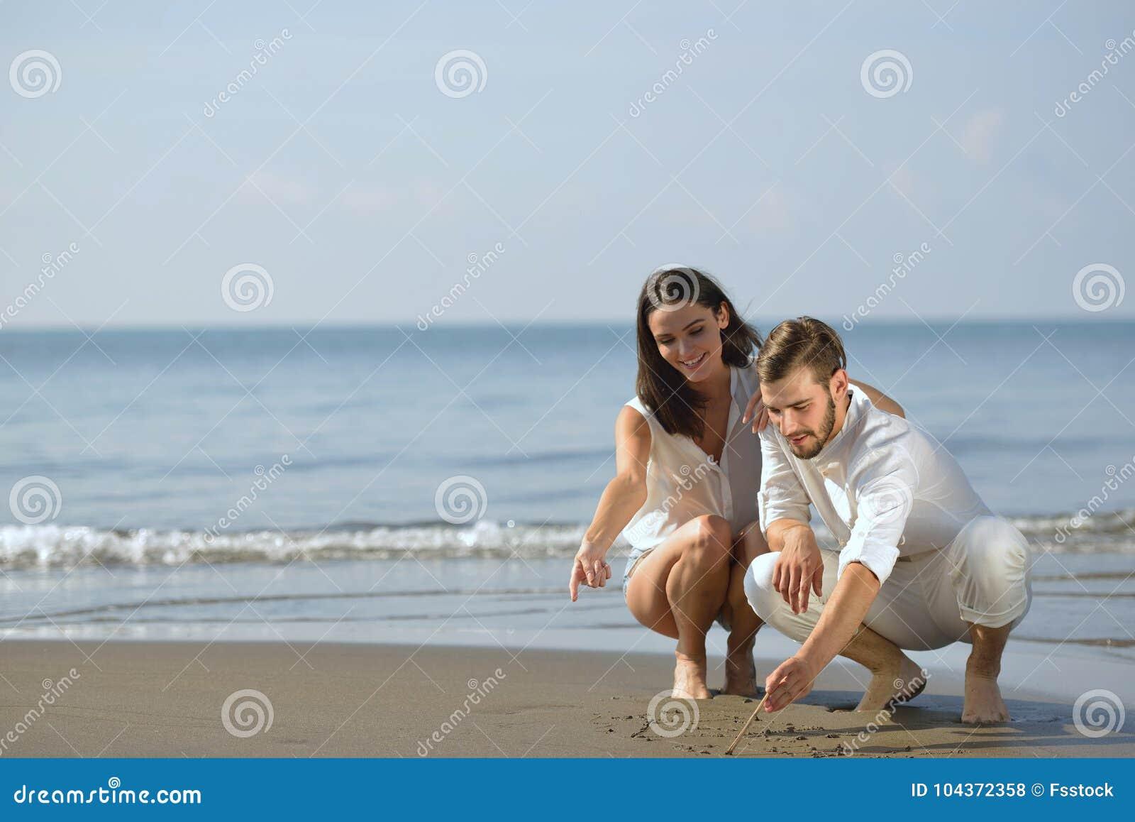 海滩概念夫妇画重点蜜月爱浪漫沙子形状夏天年轻人 夏天海滩爱概念