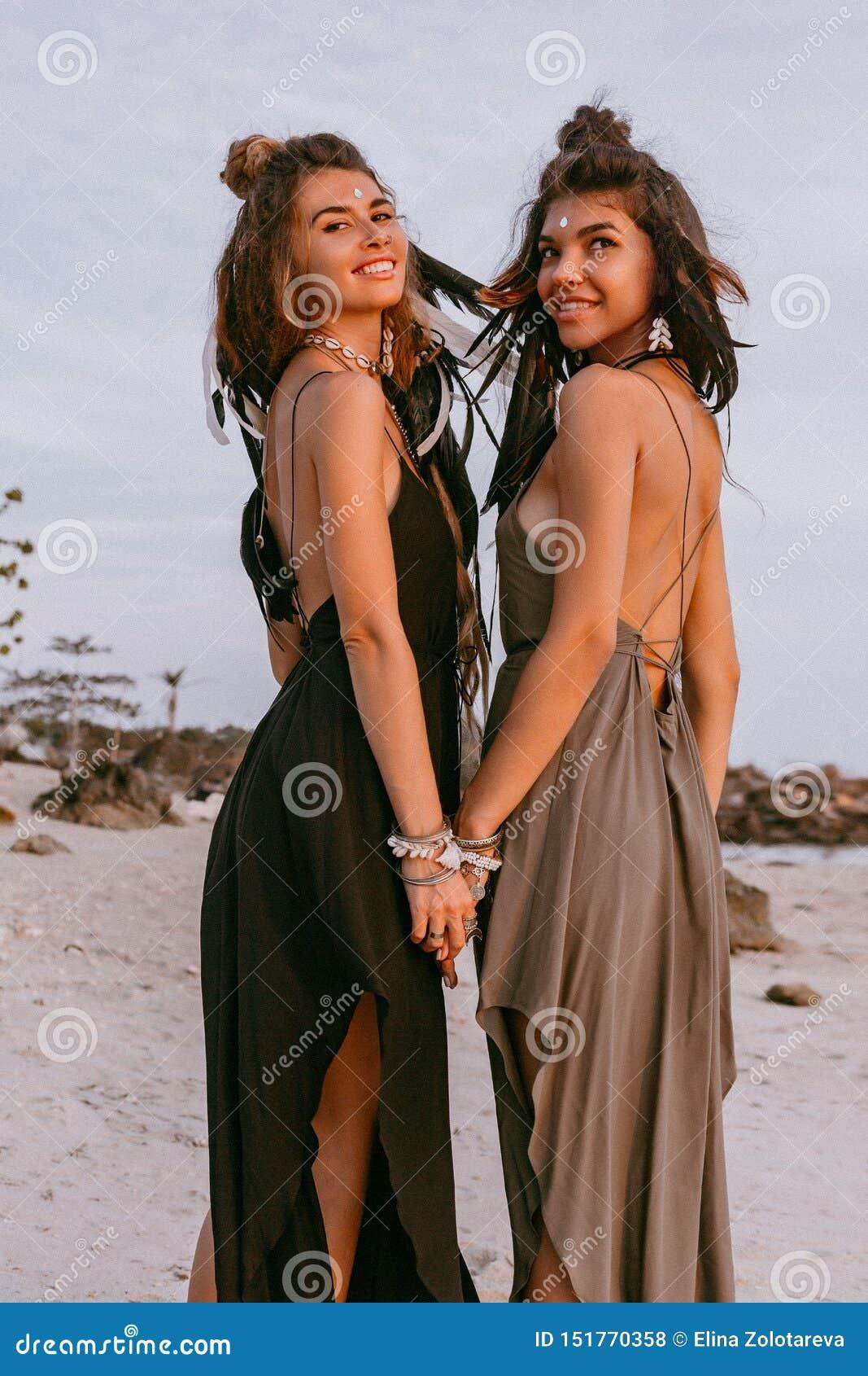 海滩的两个年轻美丽的时髦的boho女孩在日落
