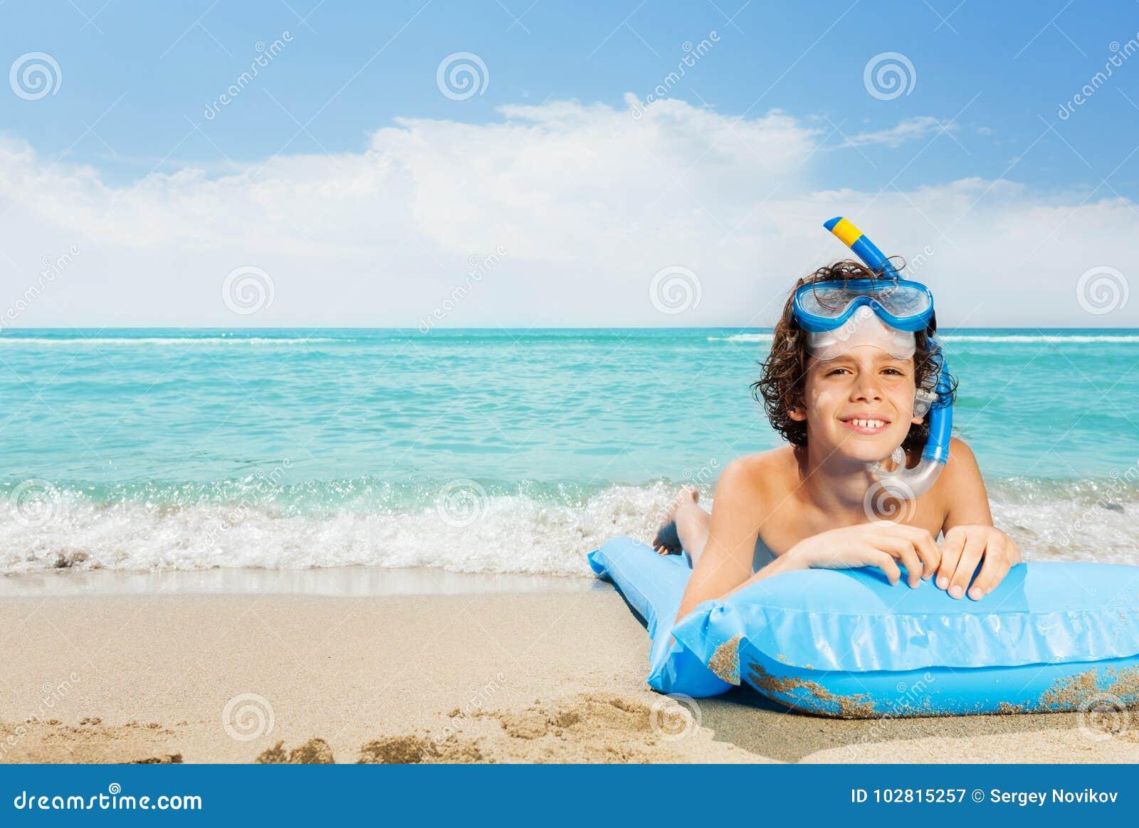 海滩的男孩与在水肺面具的可膨胀的matrass