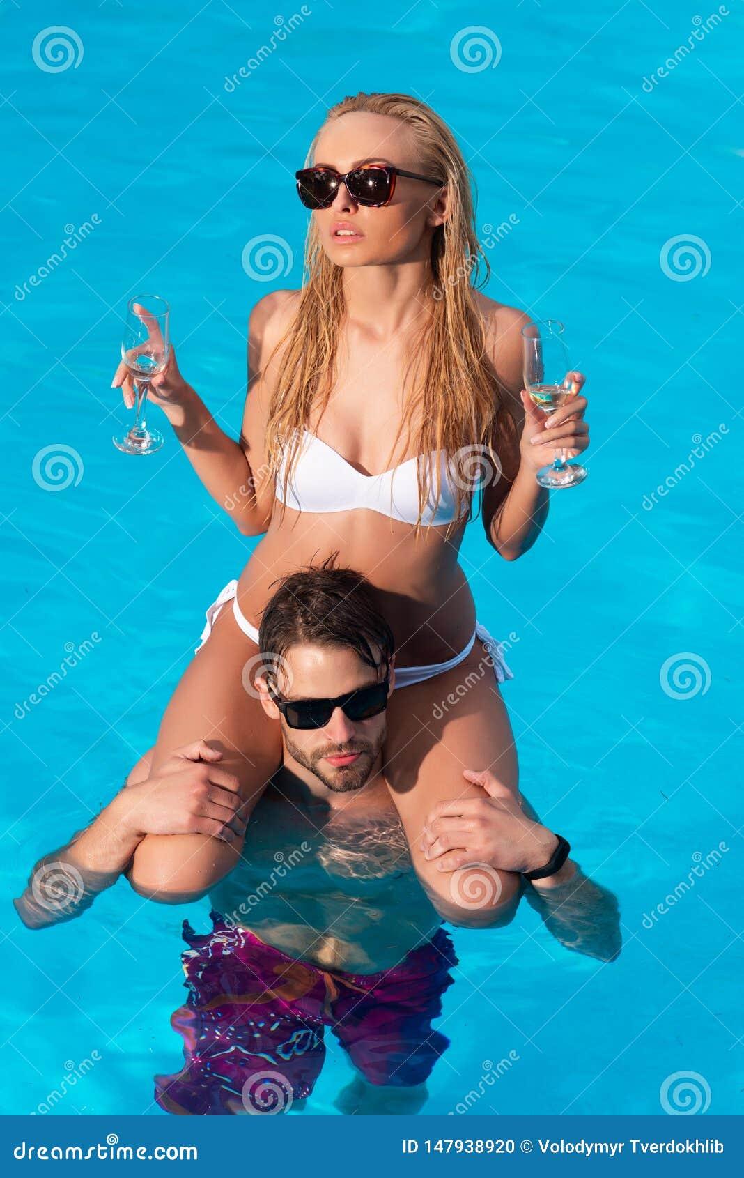 海滩的美丽的少女 性感的加上在游泳场的香槟酒 ?? 美好的年轻夫妇