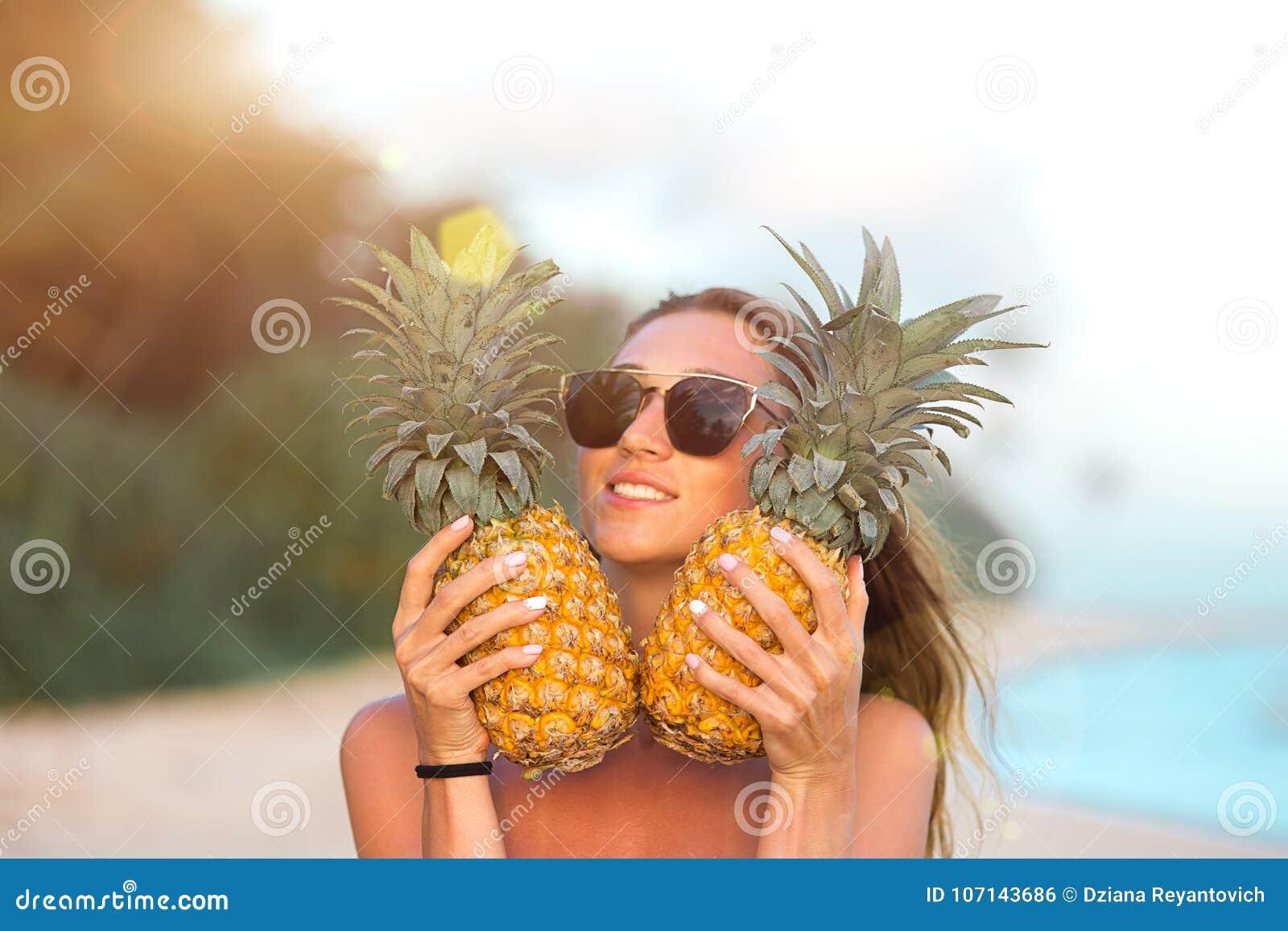 海滩的美丽的正面女孩用菠萝和棕榈树与一个有吸引力的图