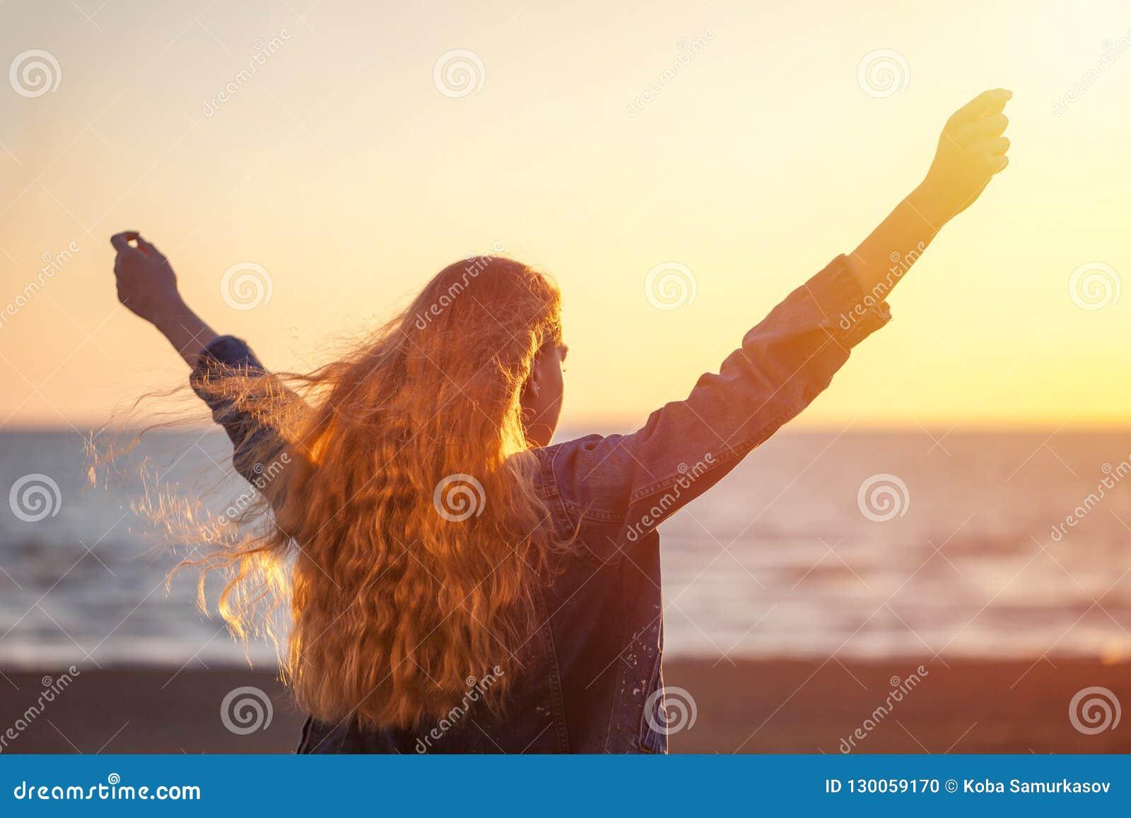 海滩的美女享受在sunse的新鲜空气自由