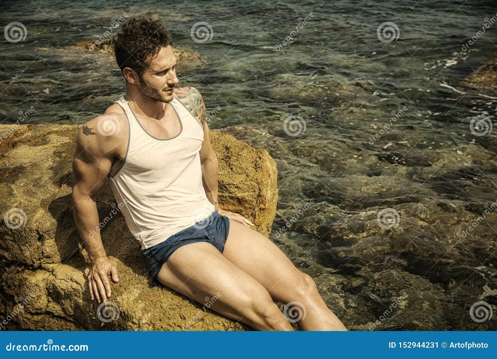 海滩的英俊的肌肉人坐岩石