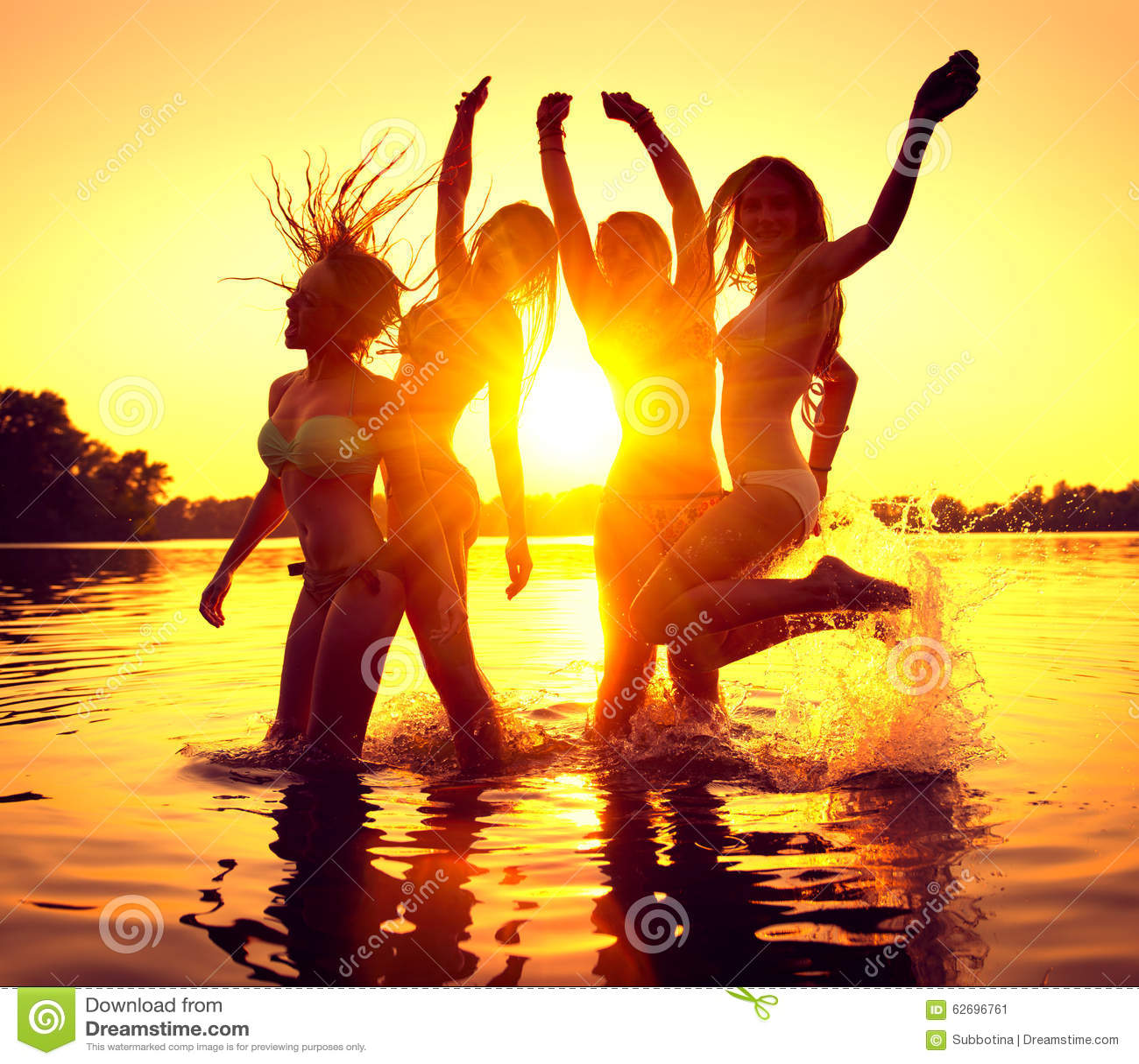 海滩党 愉快的女孩在日落的水中