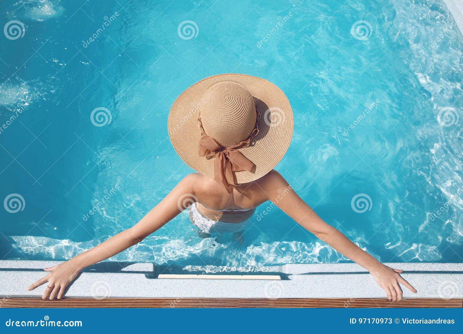 海滩帽子的享用在luxu的游泳池的妇女顶视图