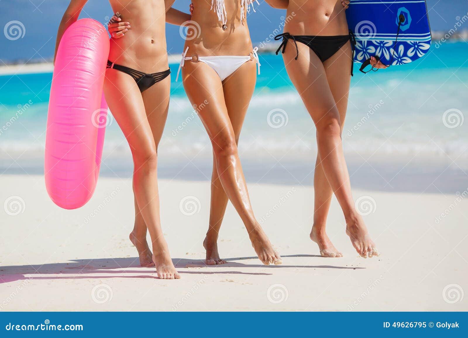 海滩的三个美丽的少妇在比基尼泳装