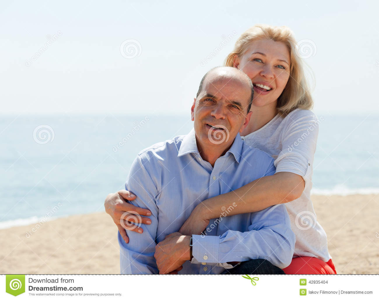 海滩的愉快的夫妇游人在假期微笑