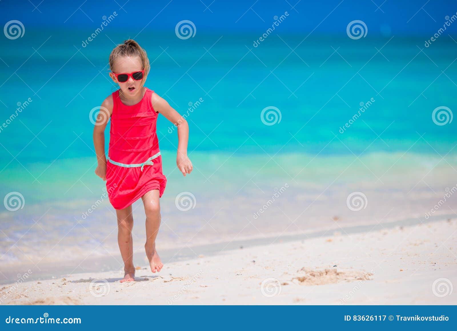 海滩的逗人喜爱的小女孩在热带假期时