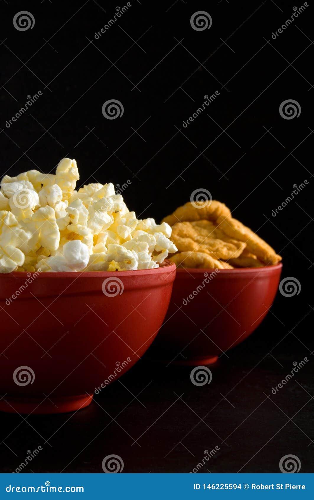 涂奶油的玉米花和BBQ米芯片接近的侧视图在黑色隔绝的红色碗的