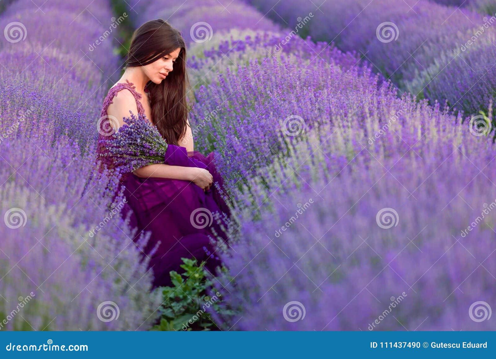 淡紫色的年轻美丽的妇女调遣以一种浪漫心情
