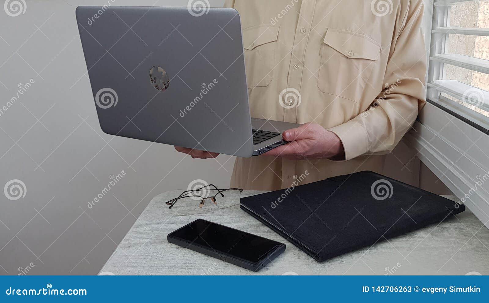 淡色的正式衬衣的一个人在角落站立在窗口附近