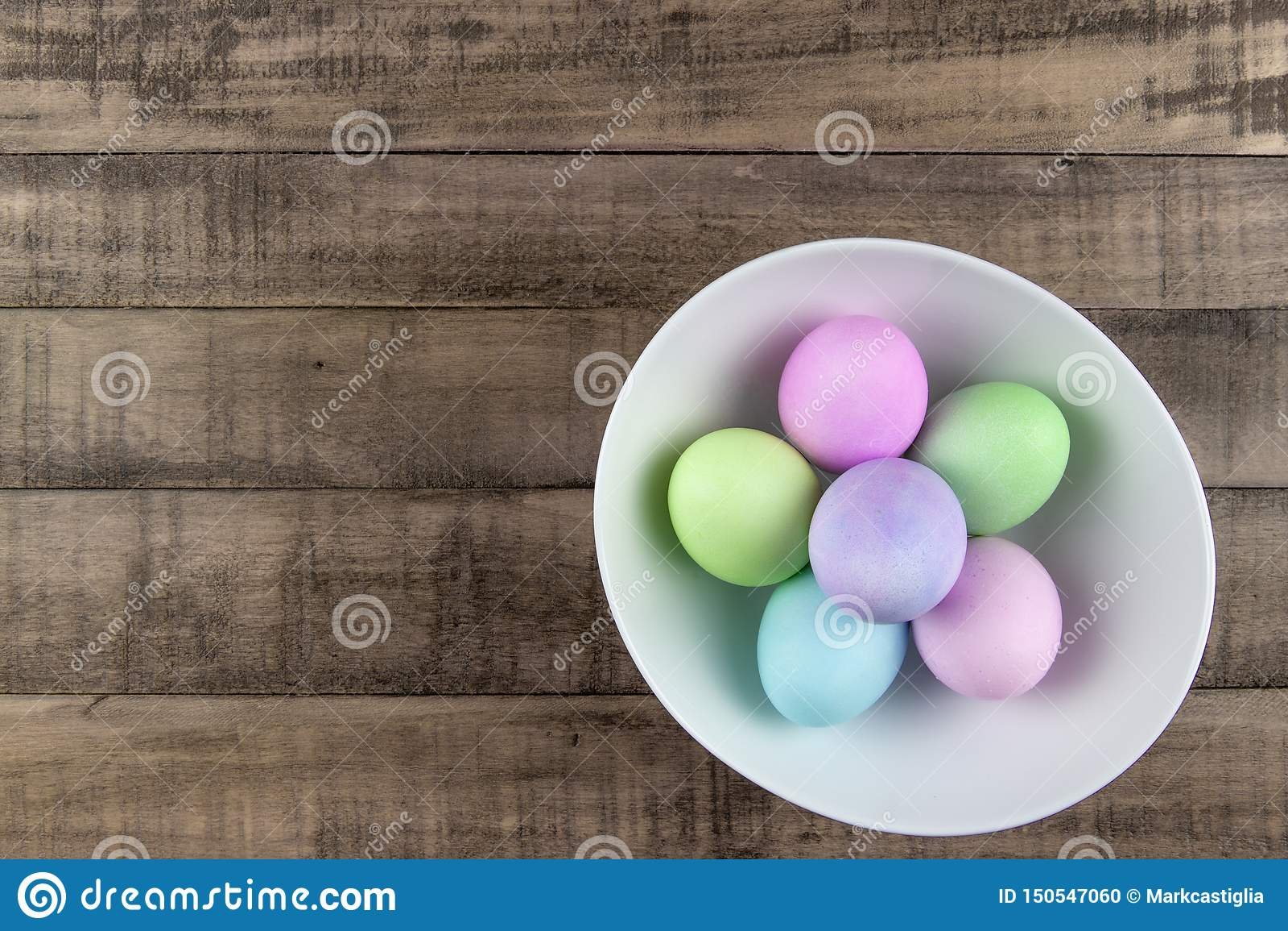 淡色被绘的复活节彩蛋顶上的看法在一个白色碗的在土气农厂桌上