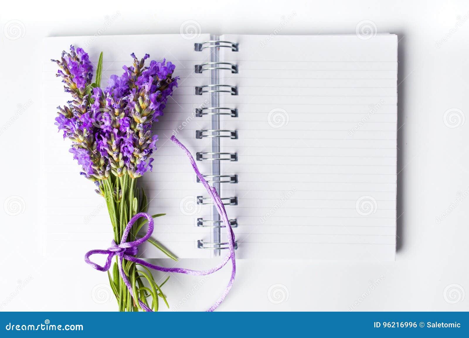 淡紫色开花在开放笔记本的花束