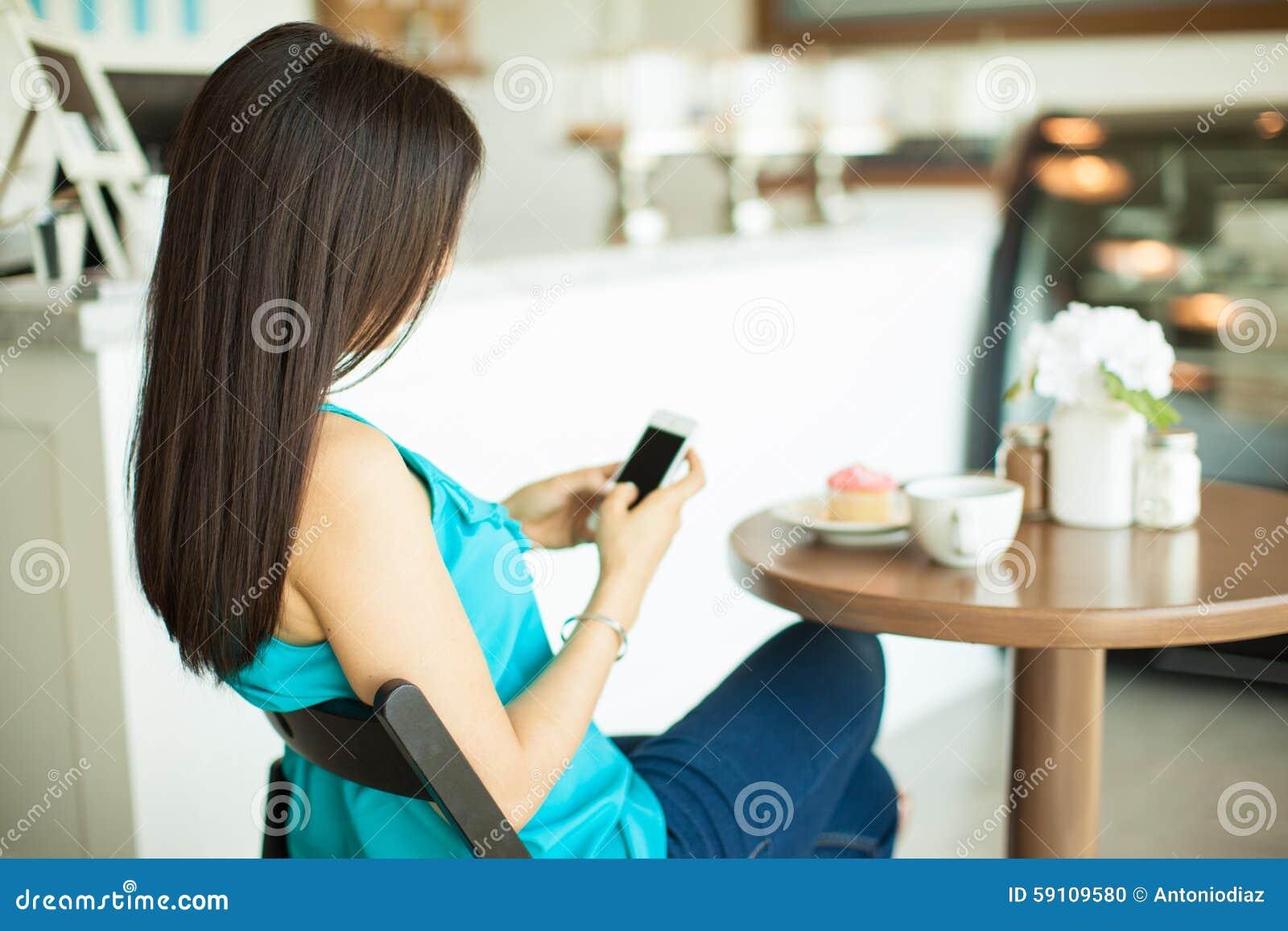 年轻深色发短信在咖啡馆
