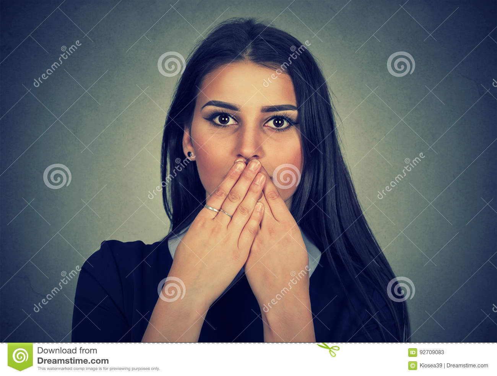 深色的妇女用手盖她的嘴