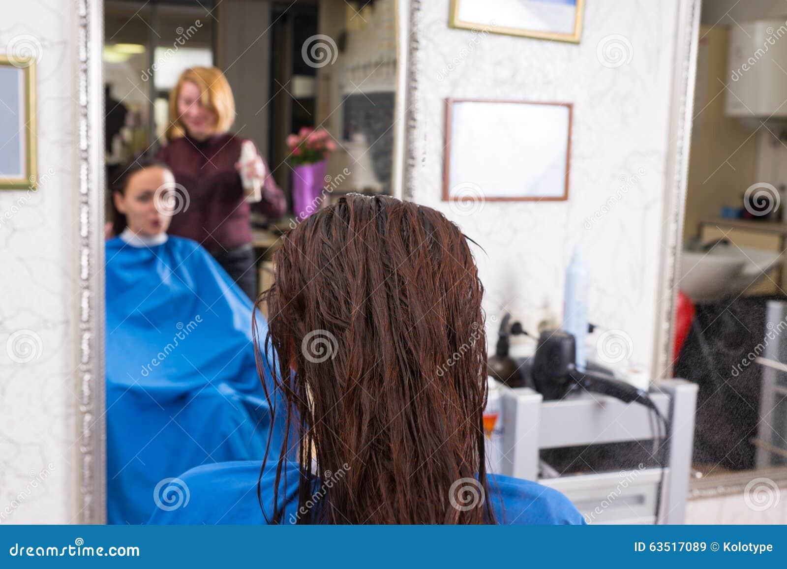 深色的妇女背面图有湿头发的在沙龙图片