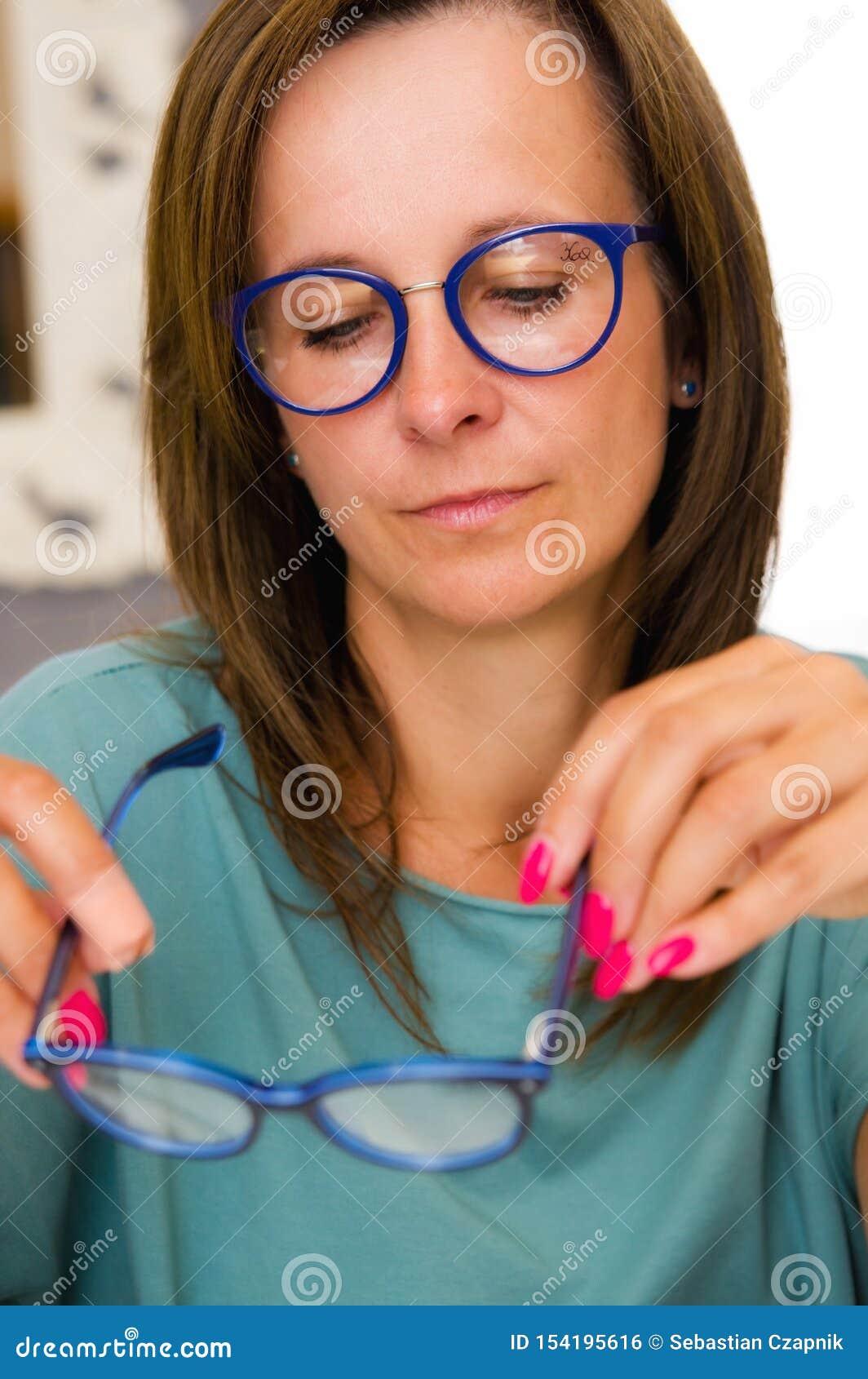 深色的妇女选择和买的镜片在眼镜师沙龙或商店
