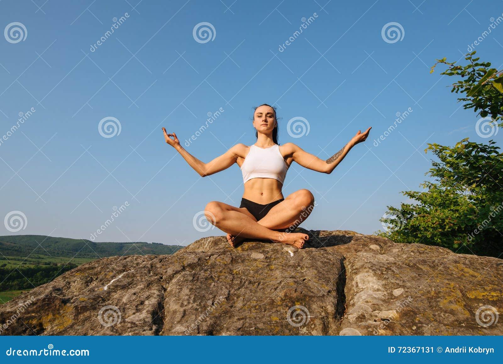 深色的妇女画象有强健的身体实践的瑜伽的在岩石 背景蓝天 和谐和放松