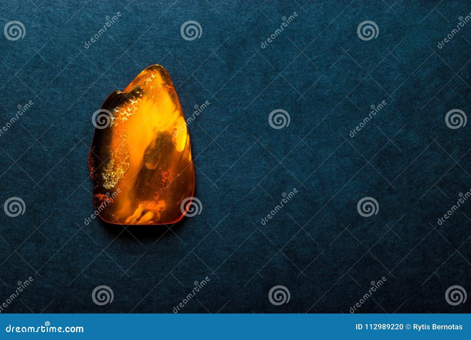 深蓝背景表面上的琥珀色的石头与自由空间